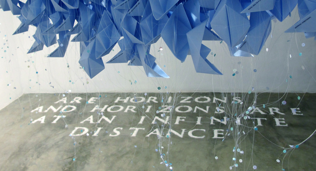 """Are horizons, and horizons are at an infinite distance"", 2014. Blue paper boats. Installation that arises from a quote from the essay ""The Inhuman"", by J. F. Lyotard, reproduced in salt on the floor. Variable measures, 7 x 2 m aprox."