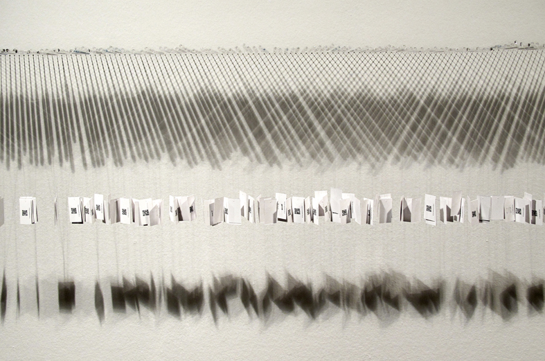 One year in minutes of silence, 2013. Glass, digital printing on paper and nylon. Variable measures.